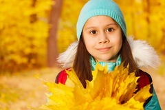 Close up view of schoolgirl with leaves bunch Royalty Free Stock Image