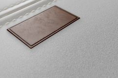 Canvas Material And Leather Label. A close up view of a section of white canvas fabric with a blank tan leather label stitched onto it - 3D render Stock Photography