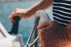 Close-up view of a Senior Man hands driving a little boat - Captain royalty free stock images