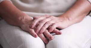 Close up view of senior woman folded wrinkled hands
