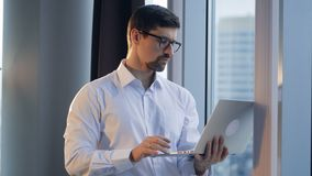 A concentrated businessman types on a laptop and looks out of a window. stock footage