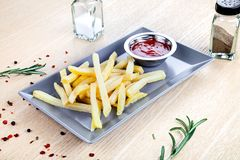 Close up view on served French fries with ketchup on white table. royalty free stock photo