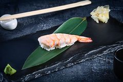 Close up view on served Nigiri with shrimp on dark plate on dark background with copy space. Delicious Ama Ebi Shrimp Nigiri Sushi stock photography