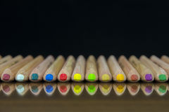 Close-up view of a set of colored pencils lying on a glass mat with reflection stock image
