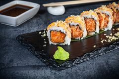Close up view on set of sushi roll. Spicy roll with salmon and caviar served on black stone on dark background. Japanese cuisine. royalty free stock photos