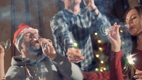 A close-up shot on people celebrating Christmas with wine and sparklers. stock video