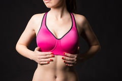 Close up view of sexy sporty woman wearing sports pink bra touching muscular stormach by hands. Royalty Free Stock Image