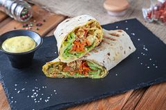 Close up view on Shawarma sandwich, gyro fresh roll in lavash. Shaurma served on black stone. Kebab in pita with copy space. stock photo