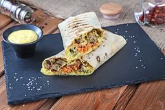 Close up view on Shawarma sandwich, gyro fresh roll in lavash. Shaurma served on black stone. Kebab in pita with copy space. royalty free stock photos