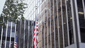 Close-up view of skyscrapers offices buildings in New York, USA. American national flag waving on the wind. Financial district of the city in downtown stock footage