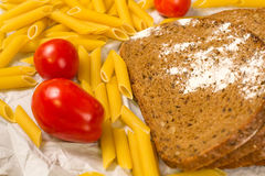 Close up view of slices of bread sprinkled with flour, Italian pasta and tomatoes on white paper Stock Images