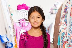 Close-up view of small Asian girl between clothes Stock Photography