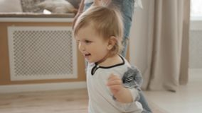 Close up view of small baby daughter walks holding her mom`s hand indoor bootlessly slow motion stock video