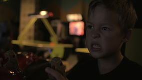 Close up view of small boy are playing video arcade game in game center. Close up view of boring tired small boy are playing video arcade game in game center stock footage