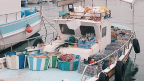 Close up view of small fishing boat. Old fishing boat moored in marina. White boat with fishing tackle. Close up view of fishing g. Ear. Small fishing boat stock video