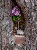 Close up view of small jesus sculpture in a tree hole. Some pink roses above sculpture royalty free stock photos
