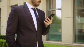 Close up view of smiling businessman dressed in shirt using smartphone while walks on the background of a modern stock video