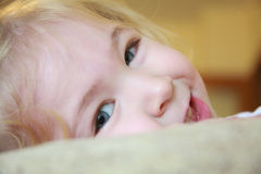 Close up view of a smiling little girl with blue eyes laying down Royalty Free Stock Photo