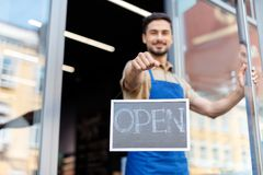 Small business owner with open sign. Close-up view of smiling male business owner holding open sign royalty free stock photos
