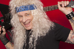 Close-up view of smiling middle-aged man holding guitar behind back Royalty Free Stock Images