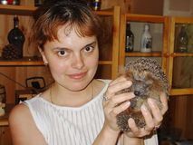 Close up view of a smiling woman holding cute hedgehog in hands. royalty free stock images
