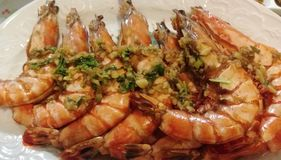 Shrimps. Close-up view of some fried big and delicious shrimps with garlic and green onion in a plate Royalty Free Stock Photo