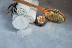 Close up view of Spa relax concept. White Terry towels, stones, candle, sea salt and wooden massage brush on a gray textured royalty free stock images