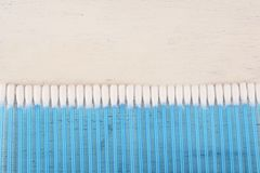 Close up view of stack of cotton buds. Stack of cotton buds on white wood background. Healthcare concept royalty free stock photography