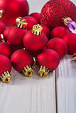 Close up view on stack of red christmas balls on wooden boards Stock Photos