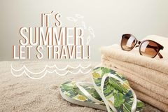 Close up view of stack of towels, sunglasses and summer flip flops on sand on grey backdrop with it is summer lets travel insp. Ection stock photography