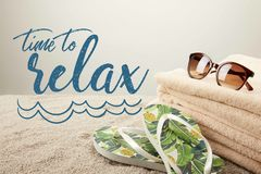 Close up view of stack of towels, sunglasses and summer flip flops on sand on grey backdrop with 'time to relax ' inspection stock image