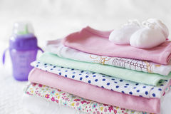 Close-up view of stacked baby clothing with a feeding bottle Royalty Free Stock Photos