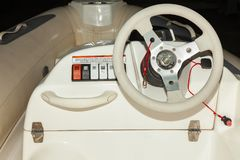 A close-up view of the steering wheel of a small white rubber motorboat with cockpit and control buttons. On the dashboard stock image