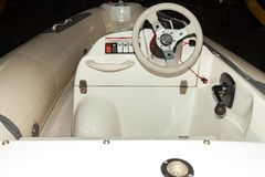 A close-up view of the steering wheel of a small white rubber motorboat with cockpit and control buttons royalty free stock photo