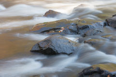 Close up view of a stony riverbed and silver stream Stock Image