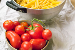 Close up view of a strainer full of Italian pasta and a cup full of tomatoes on a paper Stock Images