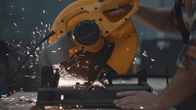 Close-up view strong hands of mechanic using electrical angular grinding machine at factory, sparks fly apart. Work in process on. Metalworking plant stock video