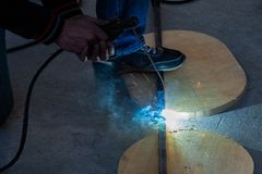 Close-up view strong man is a welder in blue working overalls without gloves on arms, a metal product is welded with a welding. Machine in the garage workshop stock photos