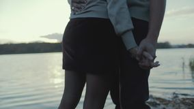 Close up view of stylish couple holding their hands and hugging each other passionately by the riverside. Forever stock footage