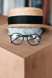 Stylish eyeglasses, scarf and straw hat in boutique Royalty Free Stock Image