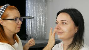 Close-up view of the stylist, the makeup artist applies a special face cream with the fingers on the face of young stock video footage