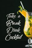 Close up view of summer fresh cocktail with mint, lemon and orange pieces, take a break drink cocktail lettering. On black royalty free stock photo