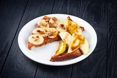 Close up view on sweet toast served on white plate on dark wooden background. fried toast with caramel, banana and apple. Food for stock images