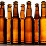 Close up view of tall beer bottles with metal caps Royalty Free Stock Images