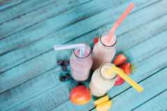 Close-up view of tasty milkshakes in glass bottles with drinking straws and fresh fruits royalty free stock images