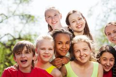 Close-up view of teenagers diversity sitting close. To each other in a hug outside during summer sunny day Stock Photo
