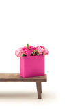 Close-up view of tender blooming rose flowers in pink paper bag on wooden bench Stock Image