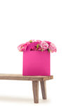 Close-up view of tender blooming rose flowers in pink paper bag on wooden bench Stock Photos