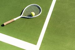 Close up view of tennis racket and ball lying on green. Tennis court stock image