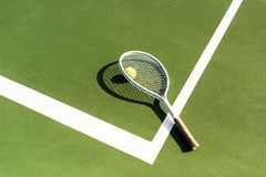 Close up view of tennis racket and ball lying on green. Tennis court royalty free stock image
